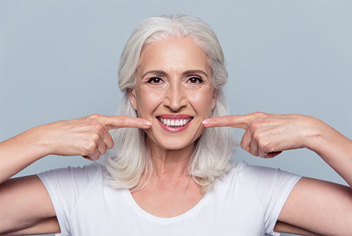 Happy senior woman pointing to dental work.